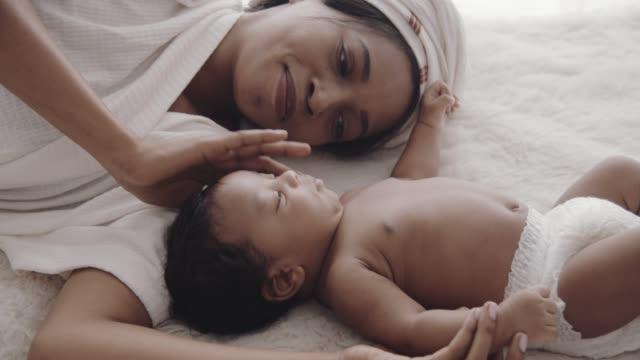 vídeos de stock, filmes e b-roll de menino africano (2-5 meses) deitado na cama com sua mãe - filha