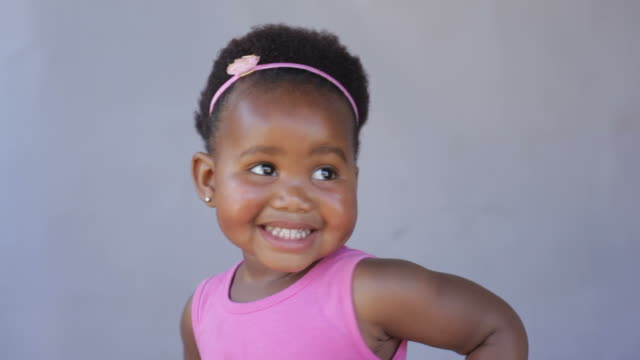 African baby girl laughing, dancing and just having fun. video
