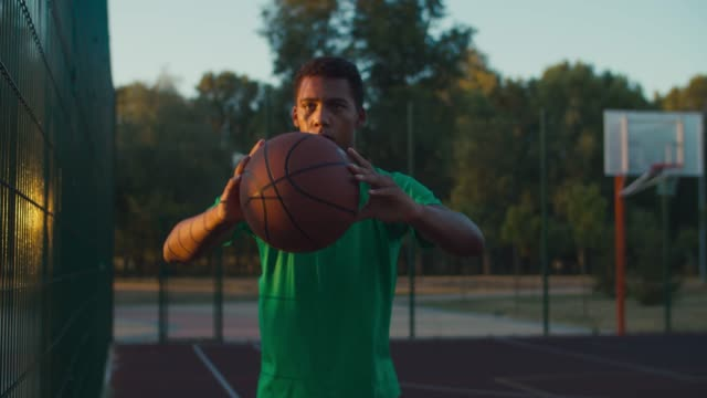 African basketball player holding ball outdoors