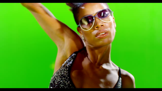 African black stylish girl dancing on green screen. Real strobe light on body. Slow motion. video