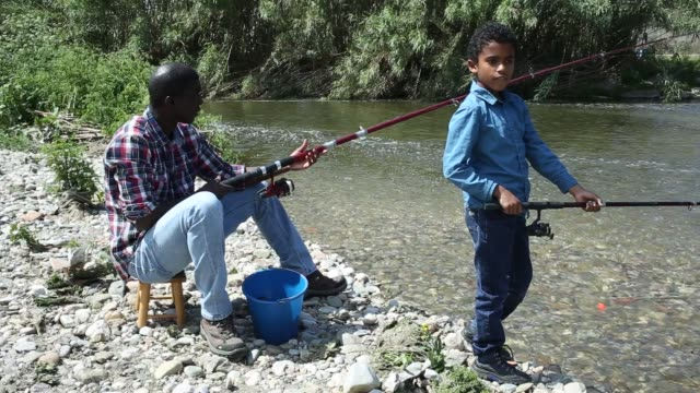 vídeos de stock e filmes b-roll de african boy and his father fishing with rods on river - fishman