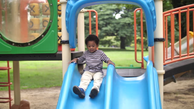 african boy at playground sliding down - scivolo video stock e b–roll