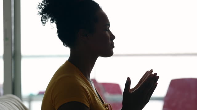 African Brazilian evangelical woman praying at home
