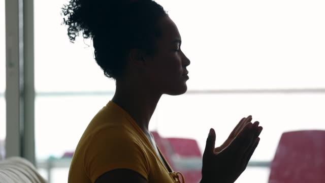 afrikansk brasiliansk evangelisk kvinna som ber hemma - kristendom bildbanksvideor och videomaterial från bakom kulisserna