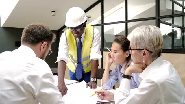 African builder presenting house blueprint to colleagues on briefing in meeting room