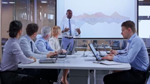 vídeos y material grabado en eventos de stock de hombre de negocios africanos de ds dando una presentación en una sala de vidrio - negocio corporativo