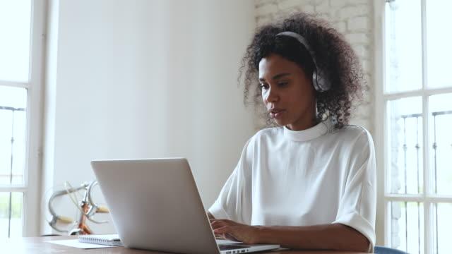 vidéos et rushes de casque africain d'homme d'affaires d'usure font l'appel vidéo sur l'ordinateur portatif - workshop