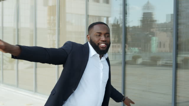 African businessman dancing in city. Business man celebrating success on street. Joyful businessman dancing in modern city. Happy african business man celebrating success on street. Smiling afro male worker dancing after successful interview outside. handsome people stock videos & royalty-free footage