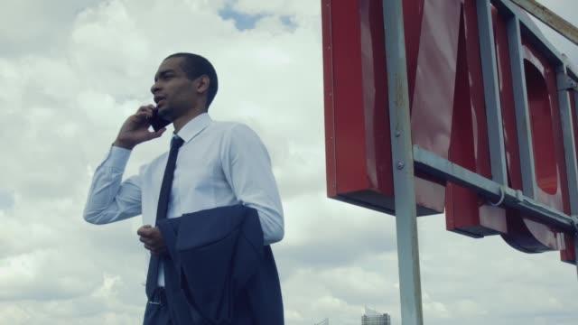 vídeos de stock e filmes b-roll de african businessman talking on cell phone. - afro americano