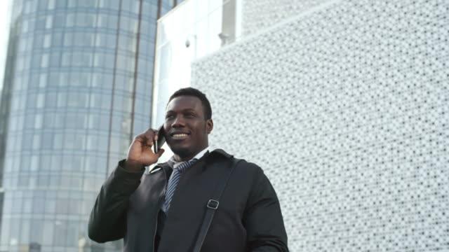 african businessman talking on phone outdoors - call center стоковые видео и кадры b-roll