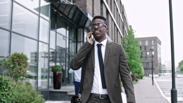 african businessman walking and talking on phone - call center стоковые видео и кадры b-roll