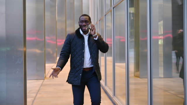 African businessman walking and using smart phone outdoors