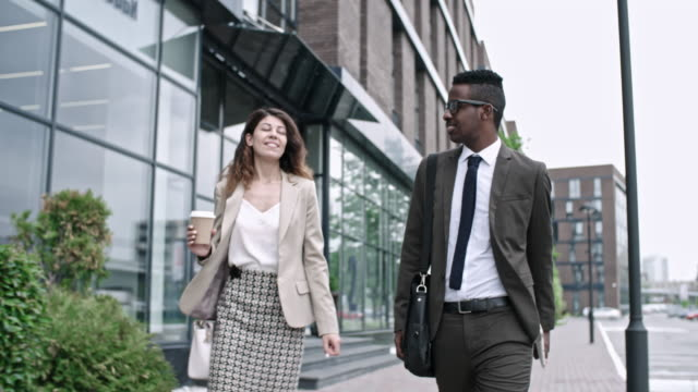 african businessman walking on the street with female colleague - collega d'ufficio video stock e b–roll