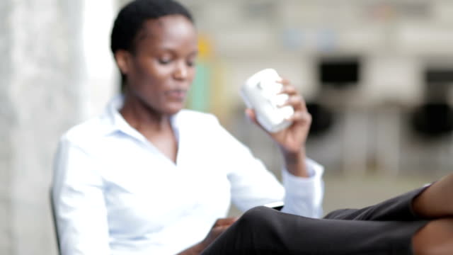 HD: African Businesswoman having Coffee Break in office texting. video