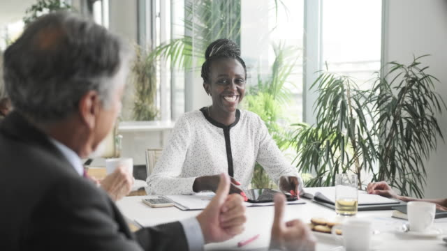 African Businesswoman Sitting at Head of Board Room Table video