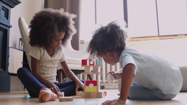 따뜻한 난방 바닥에 나무 블록을 가지고 노는 아프리카 아이들 - 완구류 스톡 비디오 및 b-롤 화면