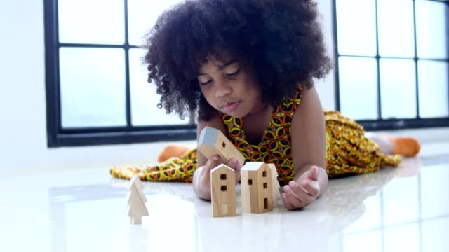 African children playing wooden blocks house on the floor.