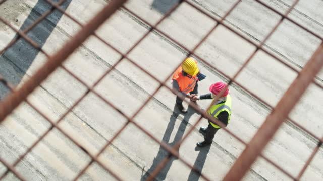 vídeos y material grabado en eventos de stock de sitio de construcción africano foreman saludo gerente caucásico - material de construcción