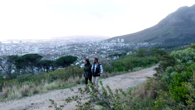 African couple hiking together on the mountain Young African couple hike above the city on Table Mountain. It is early in the morning and the sun is rising over the city. table mountain national park stock videos & royalty-free footage