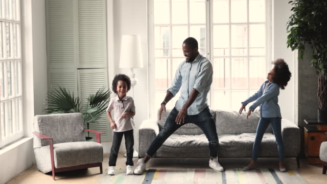 African dad dancing having fun with kids in living room Happy active african american dad teaching dancing having fun with two cute small kids son and daughter imitate father moves playing together enjoying funny weekend activity in modern living room black people stock videos & royalty-free footage