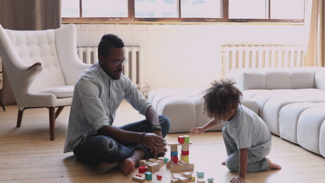 African dad teaching child son building constructor of wooden blocks Focused young single african father helping cute kid son playing on warm floor together, african family dad teaching little child boy building constructor tower or colorful wooden blocks at home block shape stock videos & royalty-free footage