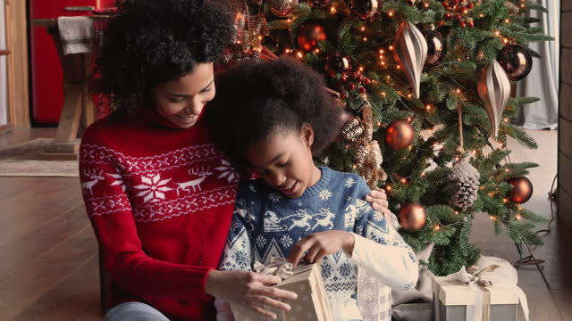 African daughter opening Christmas gift box prepared by loving mother