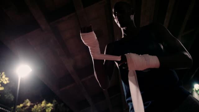 africano decente pugile mettere le sue mani con nastro adesivo - avvolto video stock e b–roll