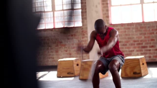 African descent man doing battle rope exercise in gym training video
