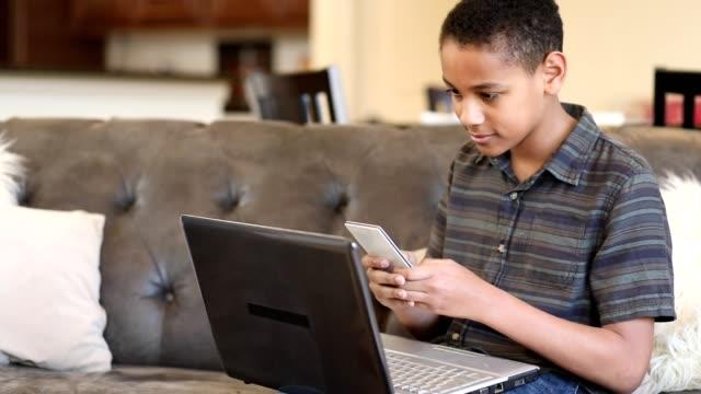 afrykański pochodzenia nastoletni chłopiec za pomocą telefonu komórkowego, laptopa w domu. - praca domowa filmów i materiałów b-roll