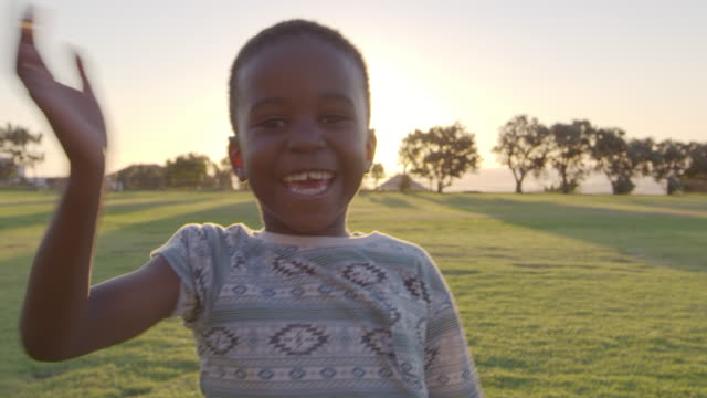 african elementary school boy waving to camera outdoors - bambine africa video stock e b–roll