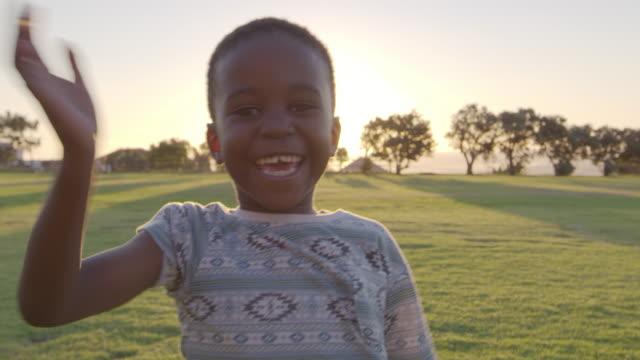 アフリカの小学生男児が屋外でカメラに手を振って - 男の子点の映像素材/bロール