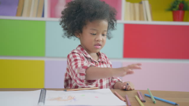 African ethnicity Child using pencil to practice drawing or writing on a book