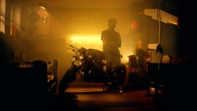 afrikaner mann auf dem motorrad in seiner werkstatt - garage stock-videos und b-roll-filmmaterial