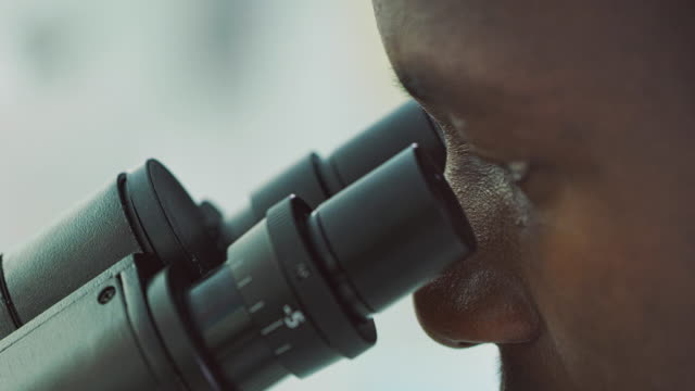 African Ethnicity man working in laboratory looks into a microscope