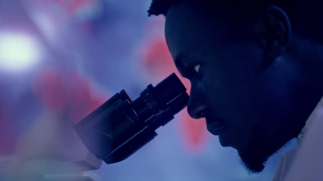 African ethnicity scientist using microscope. Pandemic cure research