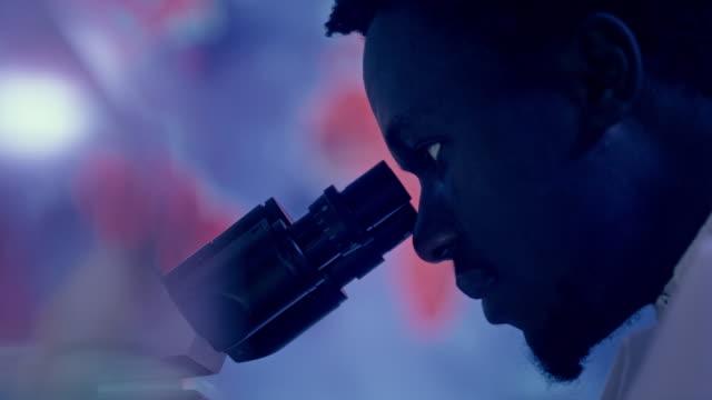 vidéos et rushes de scientifique africain d'ethnicité utilisant le microscope. recherche sur la guérison pandémique - vaccin covid