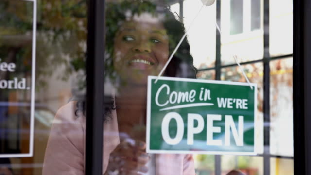 african ethnicity woman opening the store - open sign stock videos & royalty-free footage
