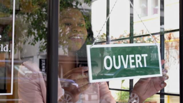 afrikansk etnicitet kvinna öppnar butiken - fransk kultur bildbanksvideor och videomaterial från bakom kulisserna