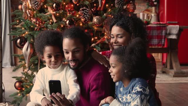 vídeos y material grabado en eventos de stock de familia africana se reunió en el árbol de navidad divirtiéndose usando el teléfono inteligente - christmas family