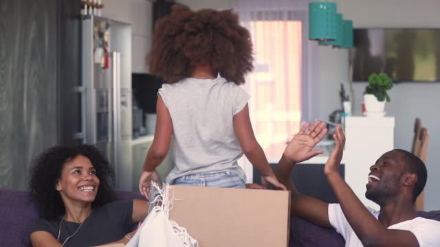 vídeos de stock, filmes e b-roll de jogo africano da família com a filha que comemora o movimento na casa nova - novo bebê