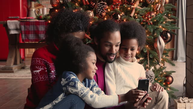 African family using smartphone having fun at Christmas decorated house