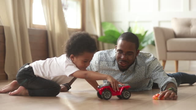 African father and little son playing with toy cars indoors