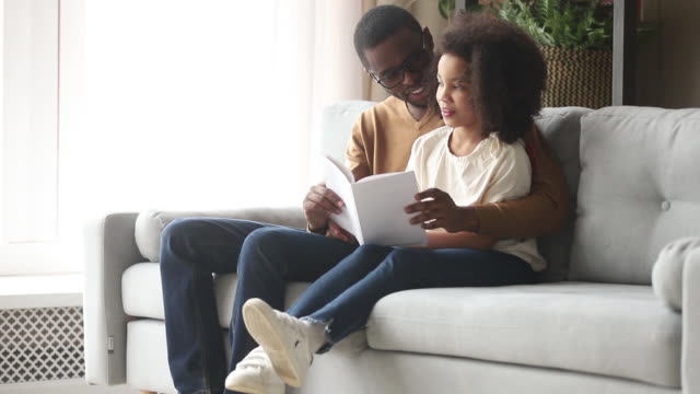 vídeos de stock e filmes b-roll de african father reading book to daughter sitting together on couch - atividade comercial
