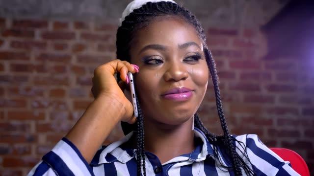 彼女の職場に坐り、スマート フォンで話すアフリカ女性のクローズ アップ - 煉瓦点の映像素材/bロール