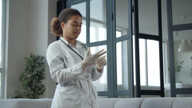 african female doctor putting on medical glove - uniform filmów i materiałów b-roll
