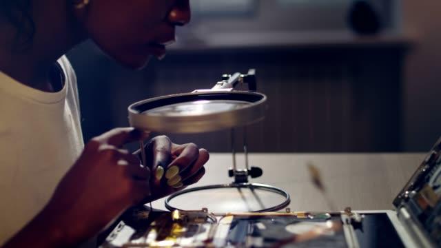 African female engeneer improving device prototype
