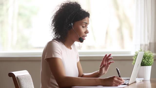 African female skype teacher wearing headset talking looking at laptop