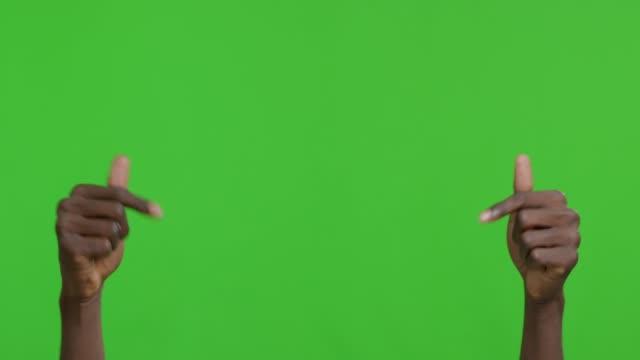 stockvideo's en b-roll-footage met afrikaanse kerel die neer met beide handen richt en gebaren duimen omhoog - hand pointing