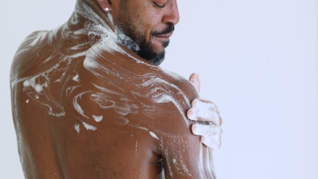 シャワーを浴びて戻って洗い戻すアフリカの男、後方のビューを閉じる - 体 洗う点の映像素材/bロール