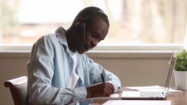 african guy wearing headset learns foreign languages online using laptop - słuchawki filmów i materiałów b-roll